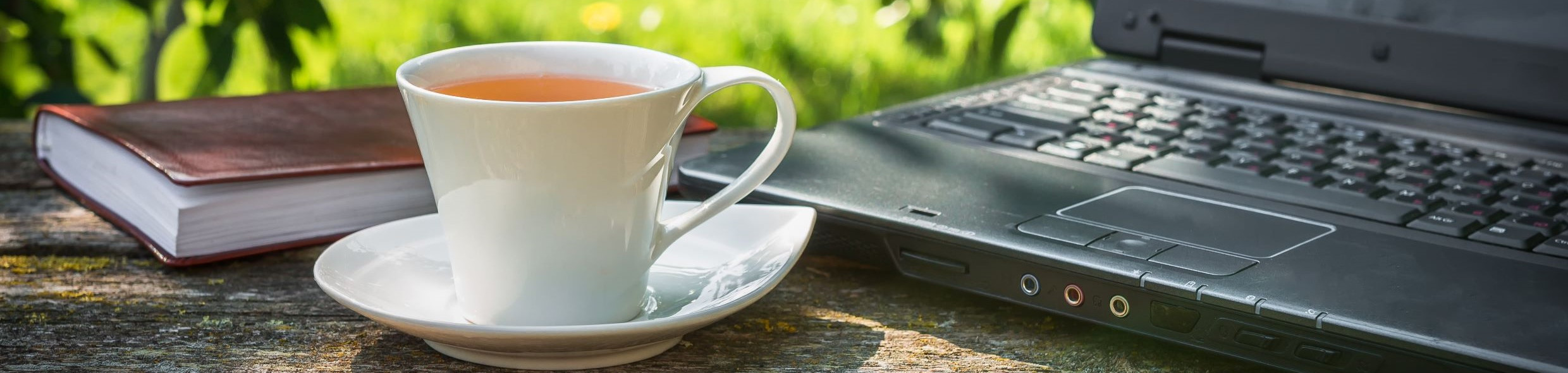 Laptop, book and cup of tea on an wooden table outdoors