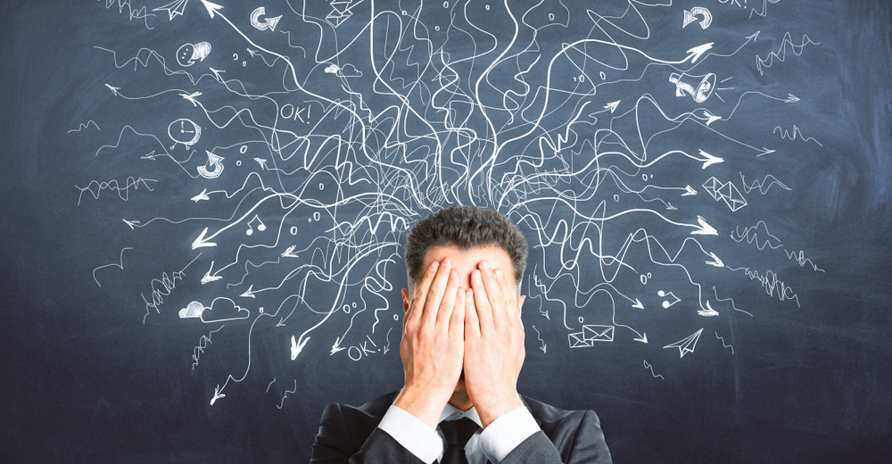 Man in suit with his hands over is eyes standing in front of a blackboard  with a messy diagram.