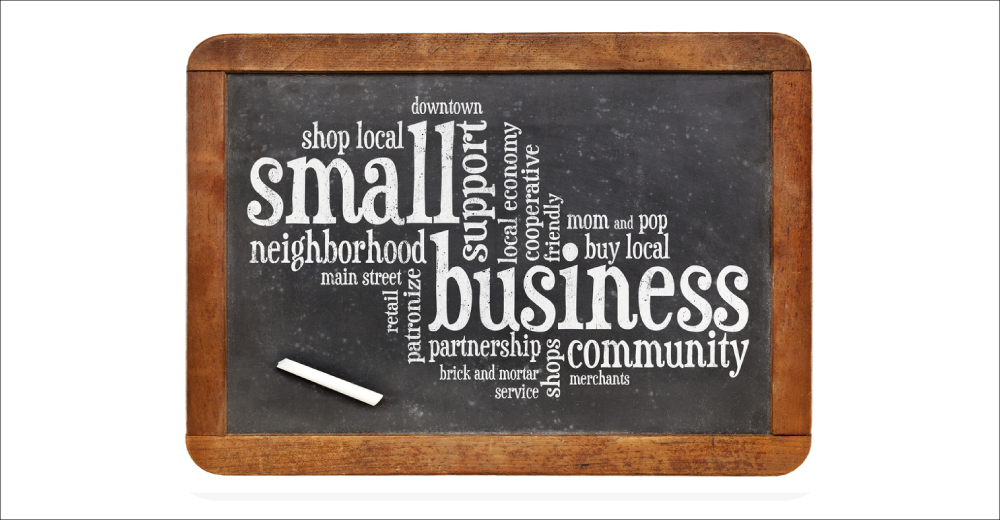 Blackboard with white chalk text promoting and supporting local businesses